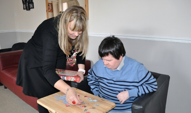 Carer helping with jigsaw